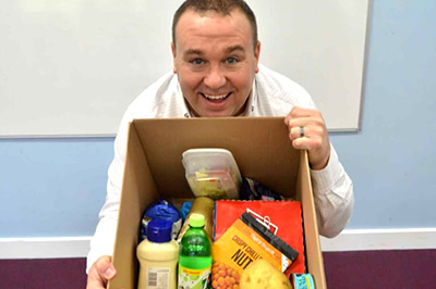 Photo of a smiling client with a box of healthy food.