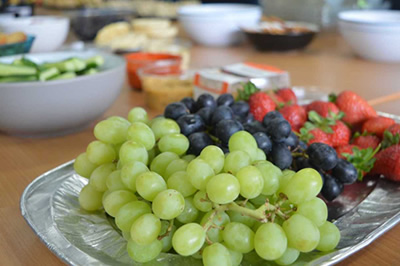 Photo of a plate with grapes, an blueberries on it.